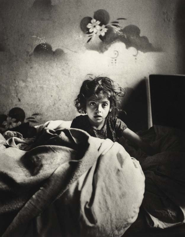 Sara, sitting In bed In a basement dwelling, with stenciled flowers above her head, Warsaw, ca. 1935–37. ©Mara Vishniac Kohn, courtesy International Center of Photography