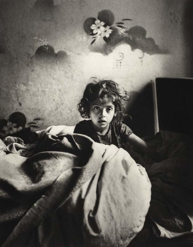 Roman Vishniac, Sara, siedząca w łóżku w mieszkaniu w suterenie, z malowanymi szablonem kwiatami nad głową, Warszawa, ok. 1935-1937, fot. © Mara Vishniac Kohn / dzięki uprzejmości International Center of Photography