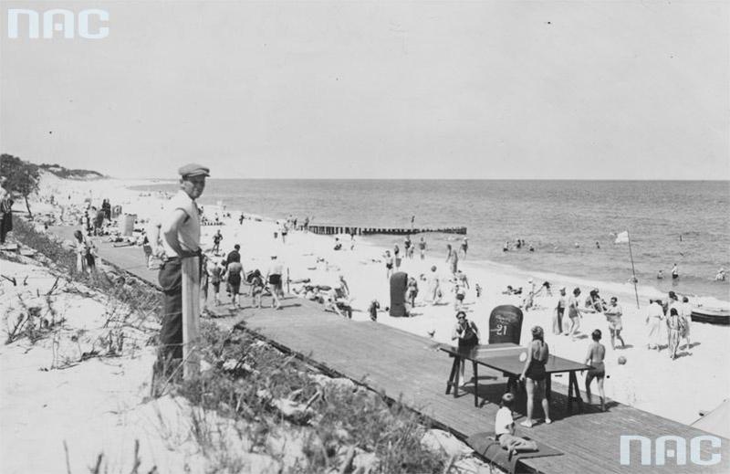 Przedwojenna Jurata. Plażowicze podczas wypoczynku. Widoczny drewniany deptak, wiklinowe kosze plażowe oraz stół do ping-ponga, 1937, fot. Narodowe Archiwum Cyfrowe