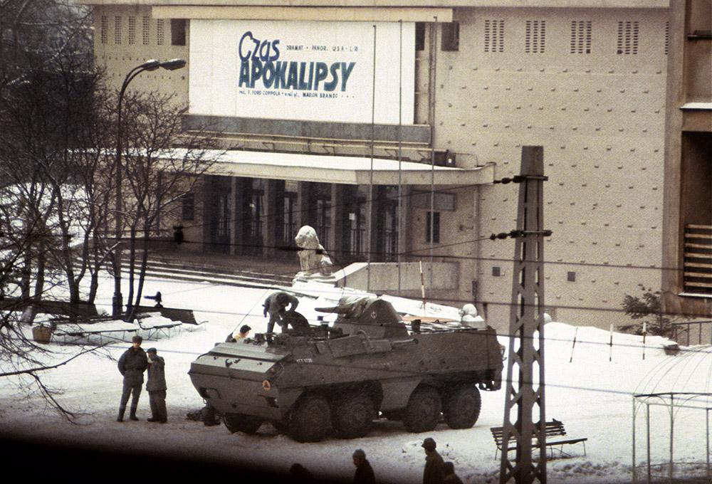 """Pierwszy dzień stanu wojennego, transporter opancerzony przed kinem """"Moskwa"""" w Warszawie i reklama filmu """"Czas Apokalipsy"""", 13 grudnia 1981, fot. Chris Niedenthal / Forum"""