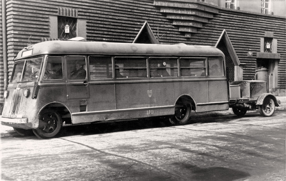 """A photograph from the album """"Warszawskie autobusy. Najpiękniejsze fotografie"""". The photograph depicts a Warsaw bus of the Chevrolet brand, transformed into a holzgas and operating in Kraków, 1940–1944, from the collection of the National Digital Archive, photo: Ewald Theuergarten / courtesy of Wydawnictwo RM"""