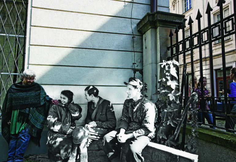 """Zdjęcie oryginalne wykonał Joachim Joachimczyk """"Joachim"""", 1 września 1944 roku, Śródmieście Północne. Powstańcy z """"Czaty 49"""" po ewakuacji kanałami ze Starówki odpoczywają na jednej z posesji przy ul. Wareckiej. Z lewej siedzi sanitariuszka Izabela Wibik """"Iza"""", fot. dzięki uprzejmości Wydawnictwa Wielka Litera"""