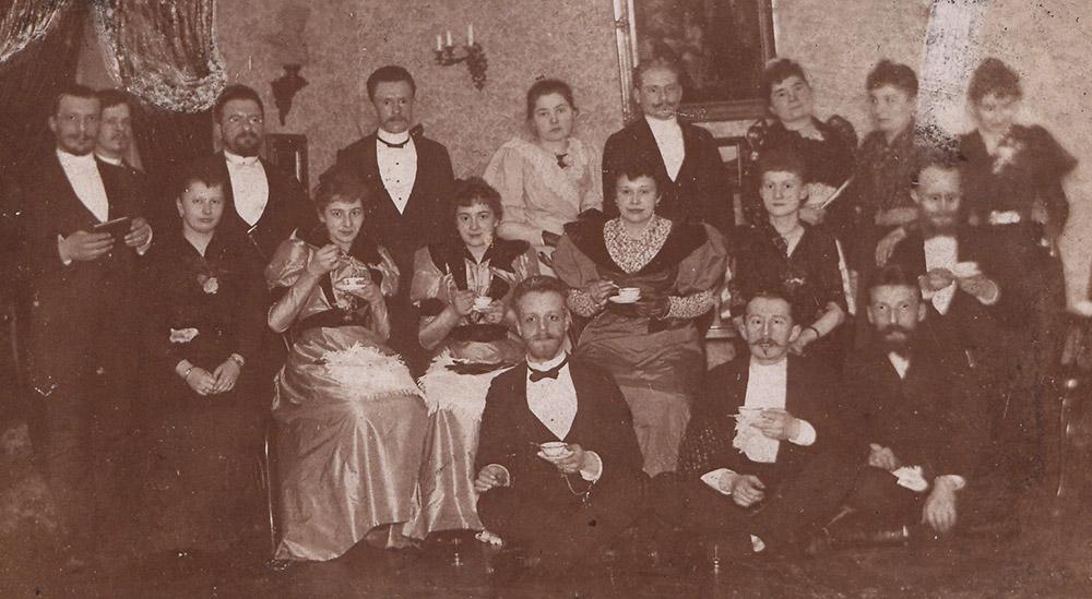 Towarzystwo w mieszkaniu pozujące do zdjęcia z filiżankami do kawy, 1900-1910, fot. Biblioteka Narodowa POLONA