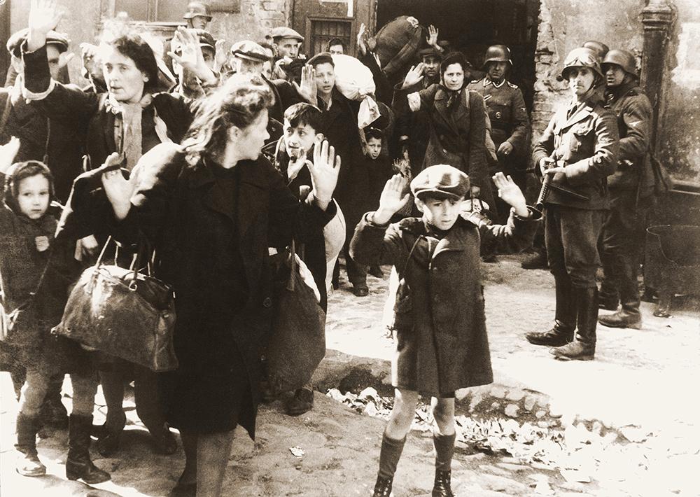 Еврейское мирное население, схваченное во время подавления восстания в Варшавском гетто. Оригинальная немецкая подпись: «Евреи, силой вытащенные из бункеров» (фотография из отчета Юргена Штрупа). Фото: wikimedia.org