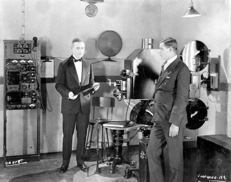 A Vitaphone projection setup at a 1926 demonstration. Engineer E. B. Craft is holding a soundtrack disc. The turntable, on a massive tripod base, is at lower center, photo: wikimedia