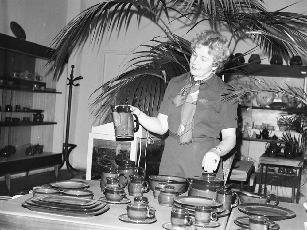 """Kobieta przy wyprodukowanych filiżankach, talerzach i imbrykach, Zakłady Porcelitu Stołowego """"Pruszków"""", 1978, fot. Grażyna Rutowska"""