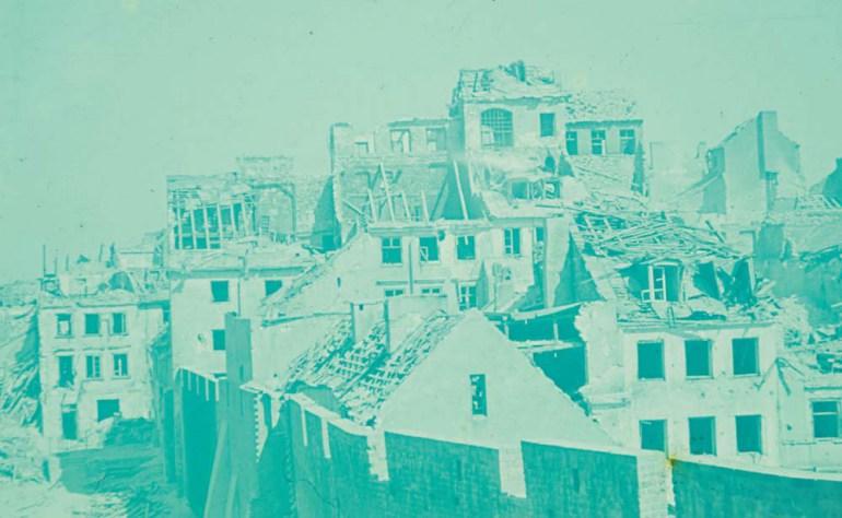 Mury obronne, zrekonstruowane w latach 30. XX wieku, i wylot ulicy Nowomiejskiej z widoczną po  lewej stronie barykadą. Po prawej typowa dla Starówki gęsta zabudowa w kwartale ulic Nowomiejskiej, Wąskiego Dunaju, Szerokiego Dunaju i Podwala, fot. Ewa Faryaszewska, slajd Agfacolor, 1944, zbiory MW