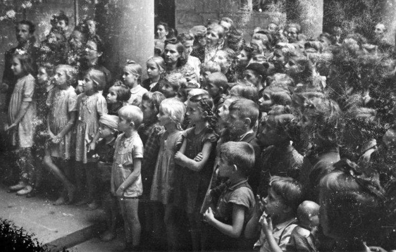 """Fotografia z Powstania Warszawskiego. Dzieci oglądające teatrzyk """"Kukiełki pod barykadą"""" 19 sierpnia 1944, Powiśle, fot. Joachim Joachimczyk """"Joachim"""" / MPW"""