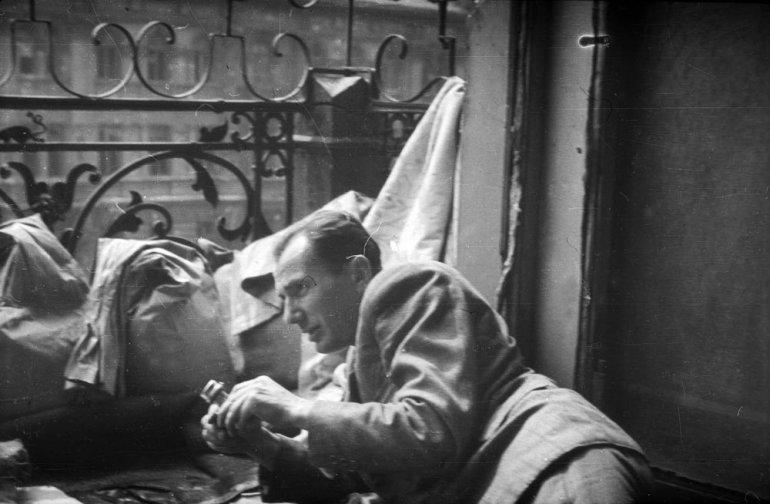 """Fotografia z Powstania Warszawskiego. Fotograf Sylwester """"Kris"""" Braun obok stanowiska CKM-u na balkonie kamienicy po parzystej stronie Alei Jerozolimskich , ujęcie z wnętrza mieszkania, ok. 17 sierpnia 1944, fot. Eugeniusz Haneman / MPW"""