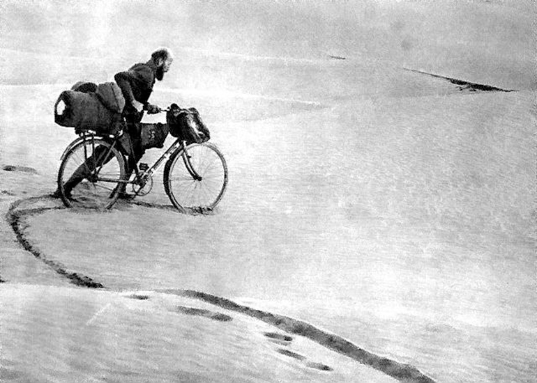Kazimierz Nowak and his bicycle on a desert in Africa. The photo probably taken by Kazimierz Nowak (1897-1937, the author is on the photo; taken probably by a self-timer) during his trip through Africa - a Polish traveller, correspondent and photographer. Probably the first man in the world who crossed Africa alone from the North to the South and from the South to the North (from 1931 to 1936; on foot, by bicycle and canoe), photo from public domain / Wikimedia