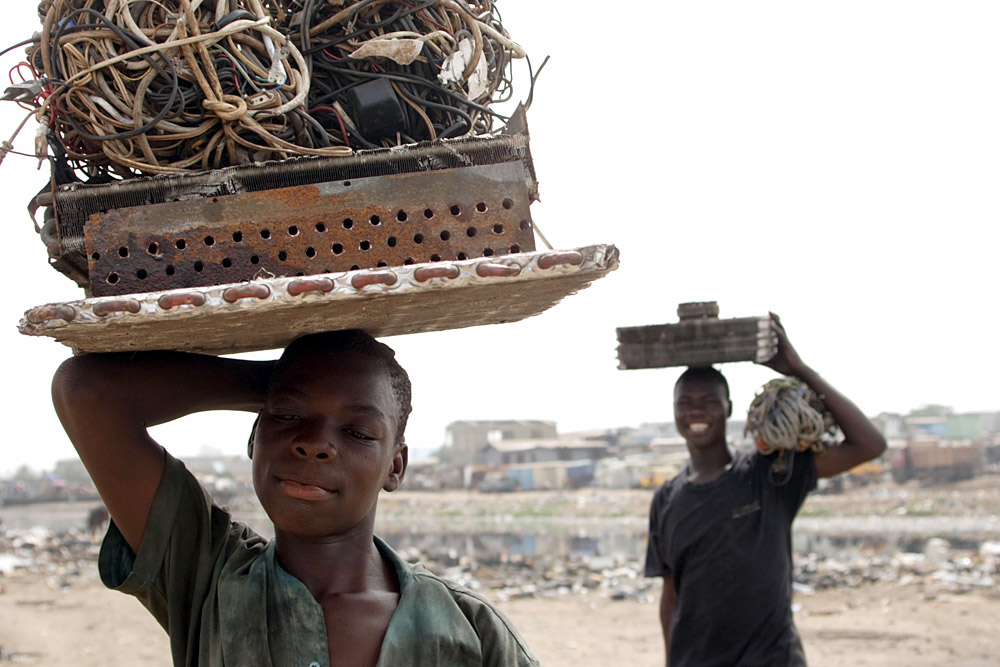 Boys carrying electronic cables from which they will extract the copper wiring by burning off the plastic in a small fire, Ghana, photo: Kate Davison/East News