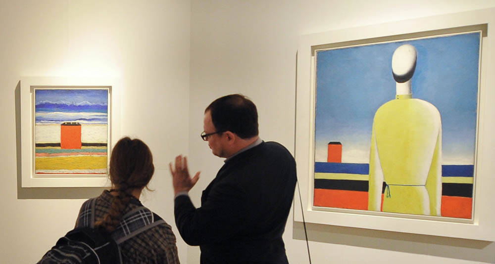 Visitors looking at a painting Torso in a Yellow Shirt (R) by Malevich at the opening of the Kazemir Malevich