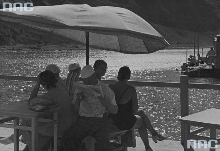 Fragment plaży. Grupa osób siedzących na pomoście przy stoliku pod parasolem. Na drugim planie widoczny pomost, 1918-1937, Zaleszczyki, fot. Wieczorek A. M.