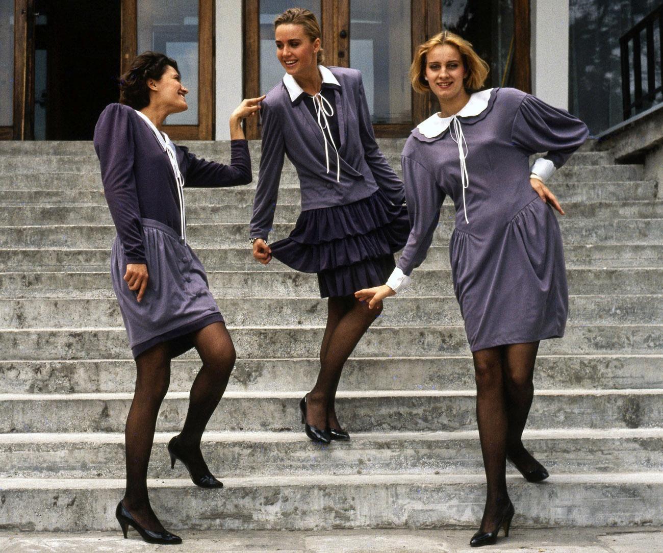 Trzy młode kobiety w fioletowych sukienkach z białymi kołnierzykami pozują na schodach.