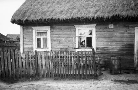 Kobieta wyglądająca przez okno wiejskiej chałupy, 1936, fot. szukajwarchiwach.gov.pl