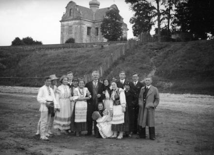Grupa osób w strojach ludowych, w tle kościół, Polesie, 1936, fot. szukajwarchiwach.gov.pl