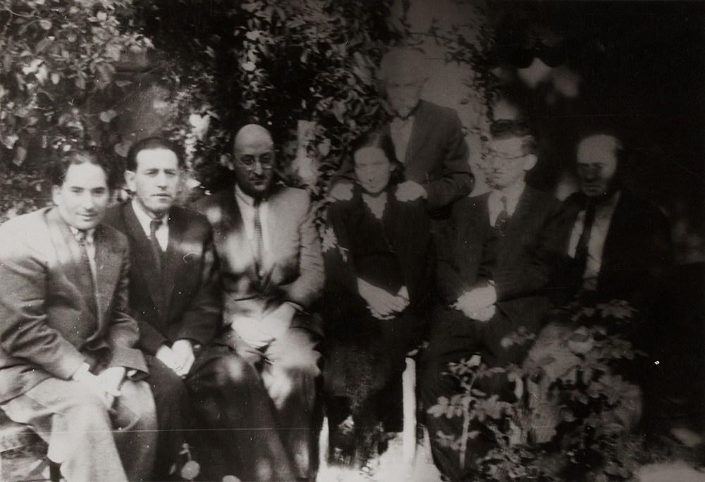 U poetki Hadasy Rubin. Siedzą od lewej do prawej strony: H. Kanaphajs, I. Aszendorf, Ber Mark, Hadasa Rubin, Dawid Rubin, I. Janasowicz, Z. Wajsman, przed 1960?, fot. Żydowski Instytut Historyczny