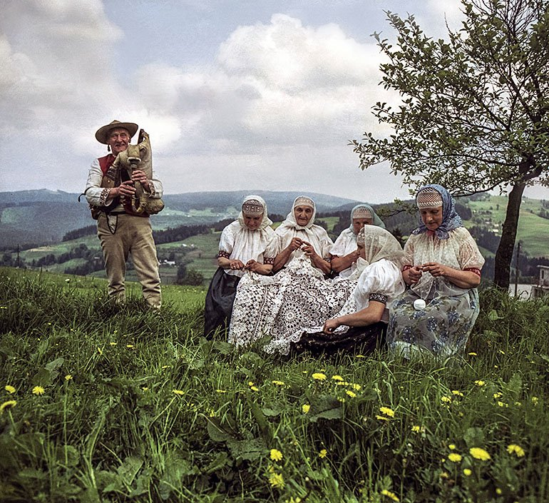The lacemakers of Koniaków,  a circle of village matrons at work in the mountains, with a view of the Beskid range in the background, and a mountaineer from the Beskid Żywiecki region playing the bagpipes, 1977, photo.: Woody Ochnio/Forum